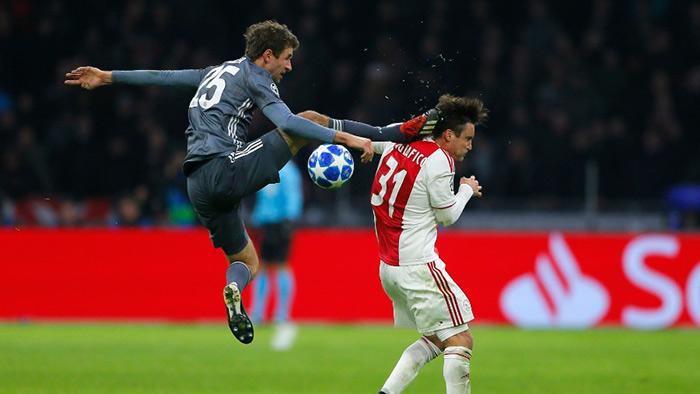 Thomas Muller da solada e Tagliafico do Ajax em jogo da Champions League